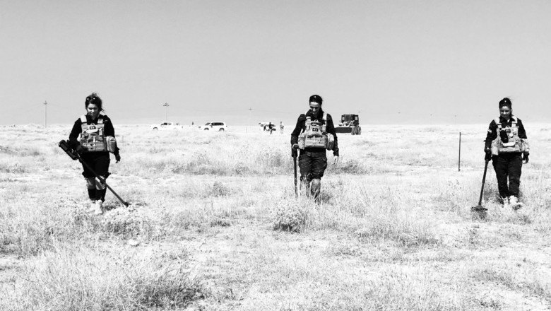Demining work clearing ISIS explosives in Sinjar Northern Iraq - photo shows three G4S employees carrying out search work